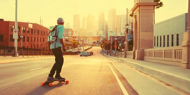 teen commuting on electric skateboard on a street