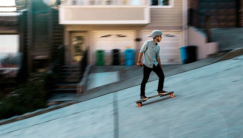young man riding on an electric skateboard uphill