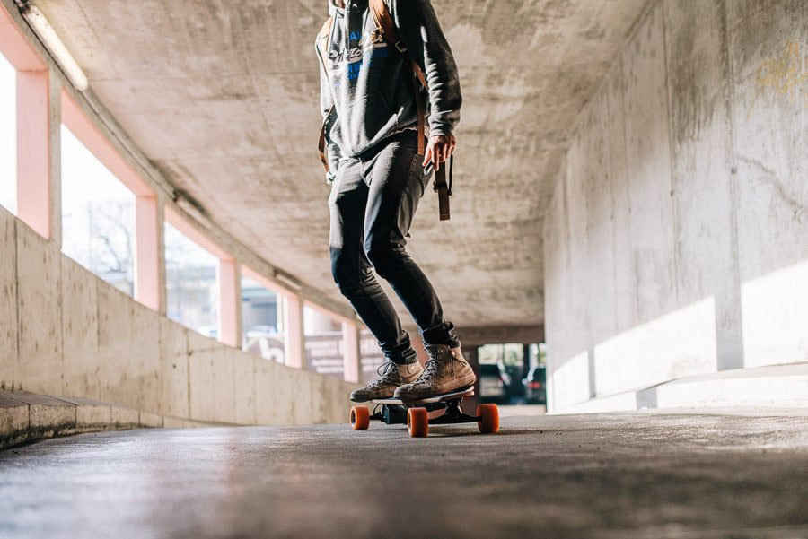 young man riding on an electric skateboard upwards a parking ramp