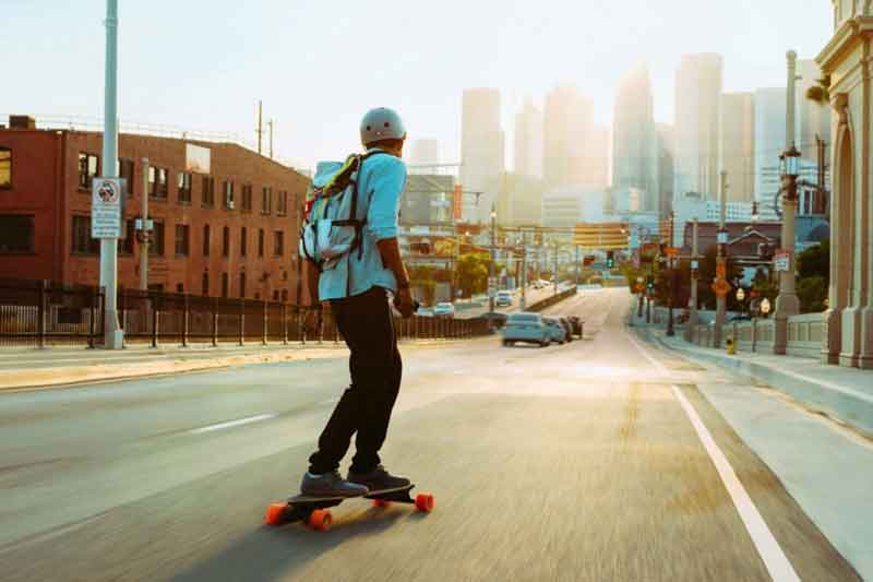 man commuting on electric skateboard through the city