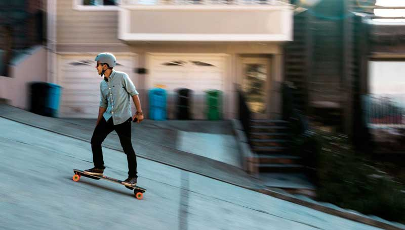 man riding on electric skateboard uphill